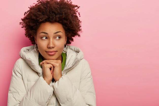 Aantrekkelijke vrouw met serieuze blik, gekleed in bovenkleding, houdt beide handen bij elkaar onder de kin, kijkt weg, probeert te verwarmen, modellen op roze achtergrond, kopie ruimte