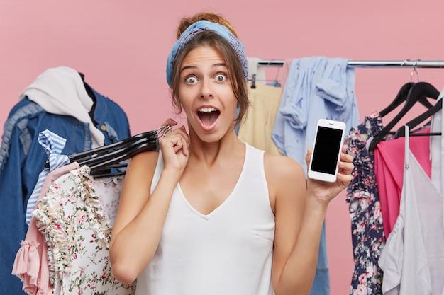 Aantrekkelijke vrouw met slimme telefoon op zoek in opwinding en shock, verbaasd over de grote verkoopprijzen in kledingwinkels, enthousiast over het kopen van kleding tegen een goedkope prijs. winkelen en consumentisme