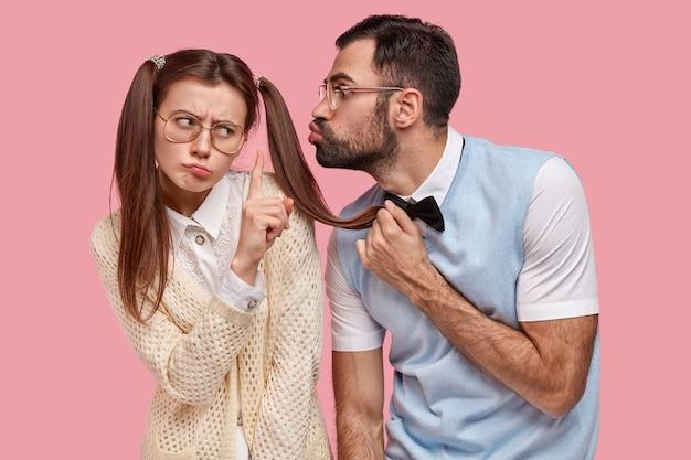 Aantrekkelijke vrouw met twee paardenstaarten weigert kus van vriendje, toont stop gebaar, draagt een grote bril, wil geen nieuwe relatie beginnen. schoolnerds poseren tijdens de date over een roze muur