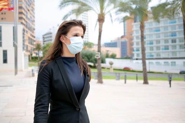 Aantrekkelijke vrouw met uitvoerende blik lopen zonder werk met beschermend chirurgisch masker