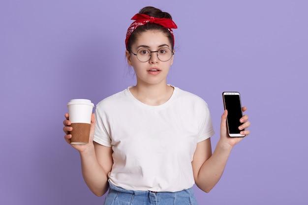 Aantrekkelijke vrouw met verbaasde gezichtsuitdrukking, houdt mobiele telefoon met leeg scherm en koffie te gaan