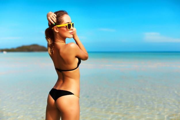 Aantrekkelijke vrouw met zwarte zwembroek en gele zonnebril