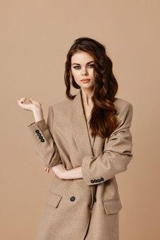 Aantrekkelijke vrouw model jas gebaren met handen op beige achtergrond kopie ruimte