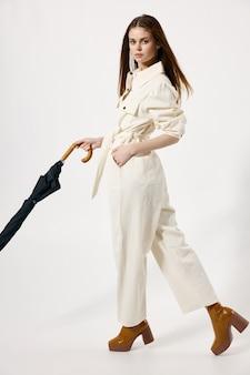 Aantrekkelijke vrouw modieuze kleding bruine schoenen paraplu in handen van regenachtig weer
