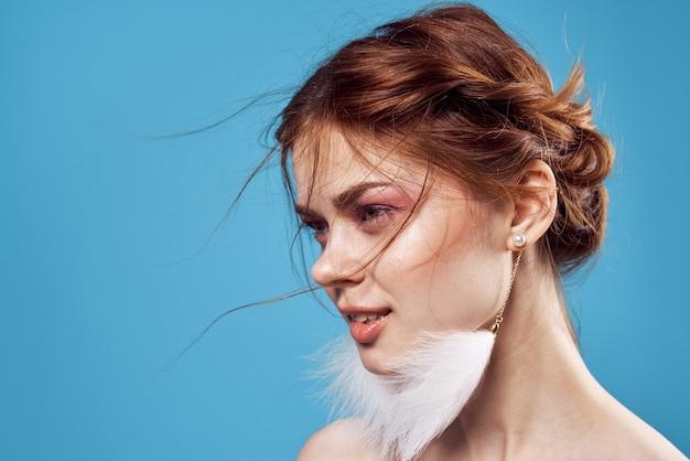Aantrekkelijke vrouw naakte schouders decoratie pluizige oorbellen lichte make-up ronde overzicht blauwe achtergrond.