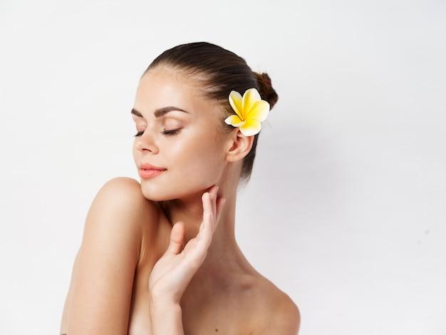 Aantrekkelijke vrouw naakte schouders gesloten ogen gele bloem in haar lichte achtergrond