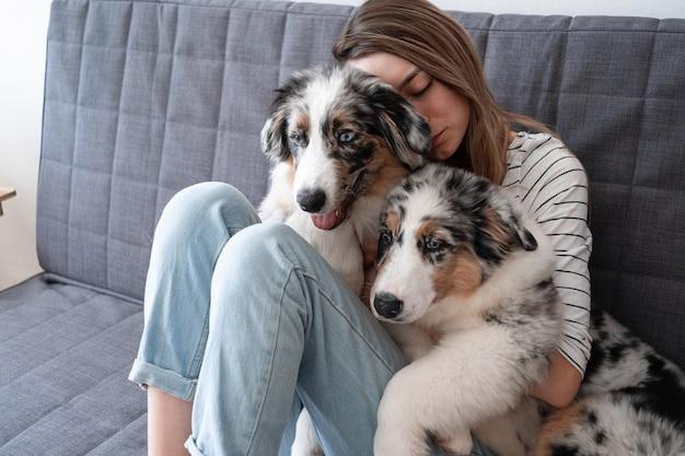 Aantrekkelijke vrouw omarmen, twee schattige australische herder blauwe merle puppy hond kussen.