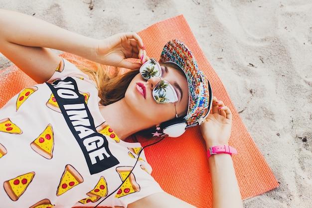 Aantrekkelijke vrouw op strand luisteren naar muziek op koptelefoon in stijlvolle kleurrijke outfit op tropische zomervakantie accessoires glb zonnebril dragen, glimlachend gelukkig liggend op yoga mat weergave van bovenaf