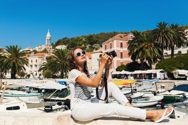 Aantrekkelijke vrouw op vakantie in europa aan zee tijdens een cruise die foto's maakt op de camera
