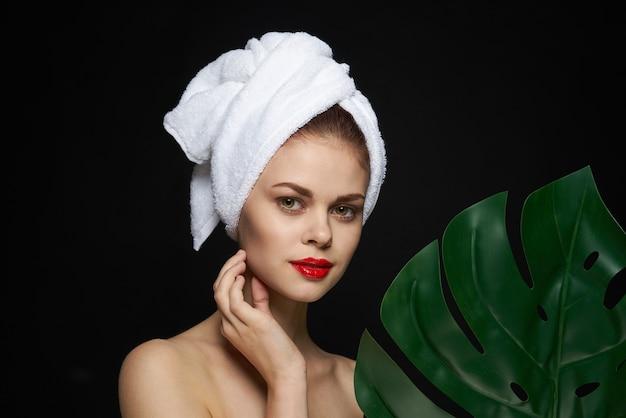 Aantrekkelijke vrouw palmblad blote schouders heldere huid donkere achtergrond