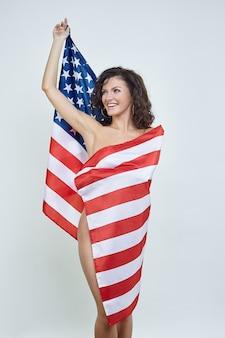 Aantrekkelijke vrouw poseren met usa vlag op witte achtergrond
