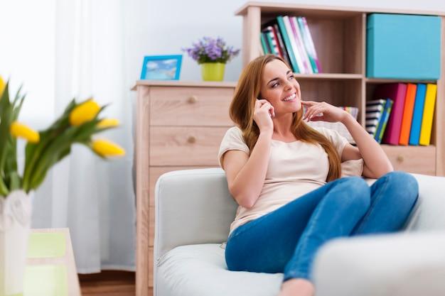 Aantrekkelijke vrouw praten via de mobiele telefoon thuis