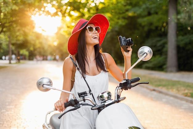 Aantrekkelijke vrouw rijden op motor in straat, zomervakantie stijl, reizen, glimlachen, gelukkig, plezier, stijlvolle outfit, avonturen, fotograferen op vintage fotocamera
