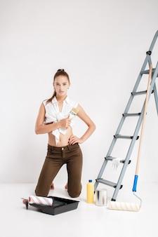 Aantrekkelijke vrouw schilderij muur in haar huis. mooie vrouw met een kwast