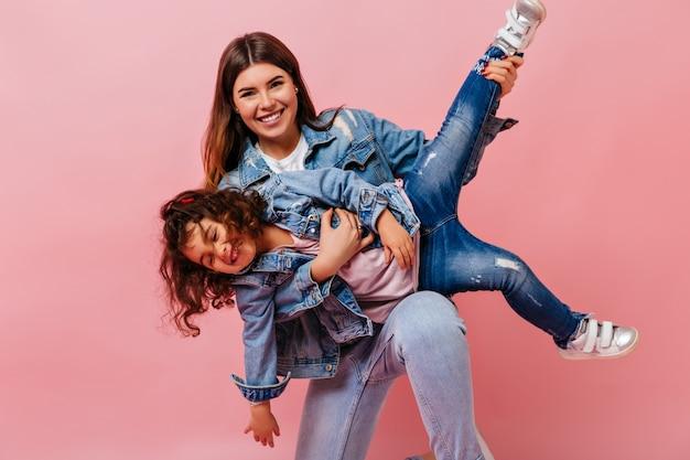 Aantrekkelijke vrouw speelt met dochtertje op roze achtergrond. studio shot van moeder en preteen kind in spijkerjasjes.