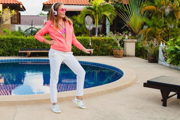 Aantrekkelijke vrouw sporten bij zwembad in kleurrijke roze hoodie dragen van een zonnebril luisteren naar muziek in koptelefoon op zomervakantie, tennissen, sport stijl