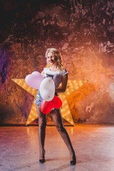 Aantrekkelijke vrouw sta op ster met ballonnen