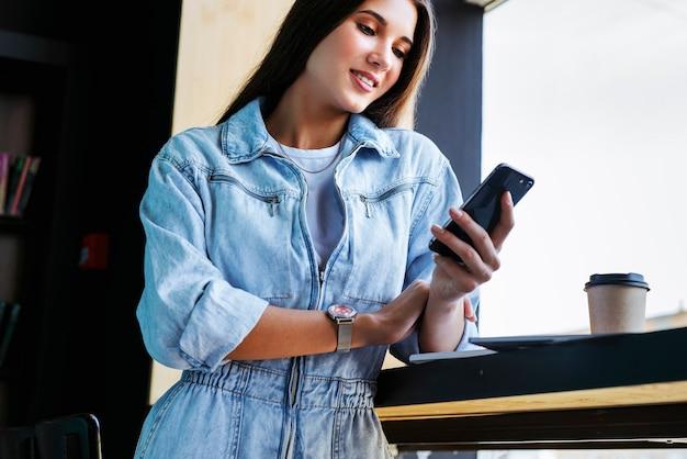 Aantrekkelijke vrouw staat in de buurt van het raam, leunend op de tafel en houdt een smartphone in haar hand.