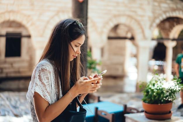 Aantrekkelijke vrouw staat met telefoon. het meisje typt een bericht.