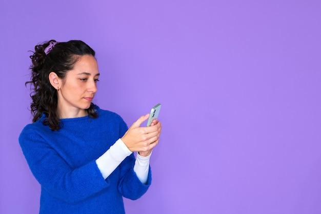 Aantrekkelijke vrouw texting op haar telefoon. paarse achtergrond en kopie ruimte. het meisje draagt een blauwe trui. gekruld haar.
