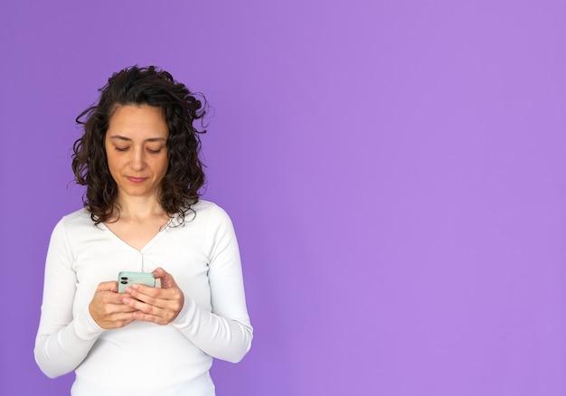 Aantrekkelijke vrouw texting op haar telefoon. paarse achtergrond en kopie ruimte. wit casual overhemd. gekruld haar.
