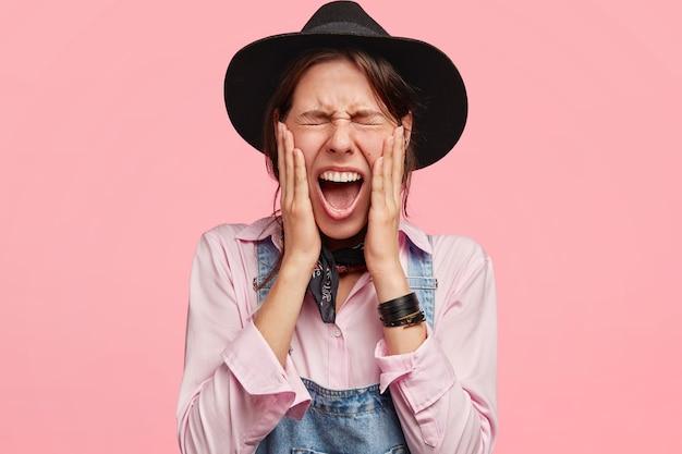 Aantrekkelijke vrouw tuinman houdt de ogen dicht, opent mond wijd, raakt wangen, draagt hoed en overall