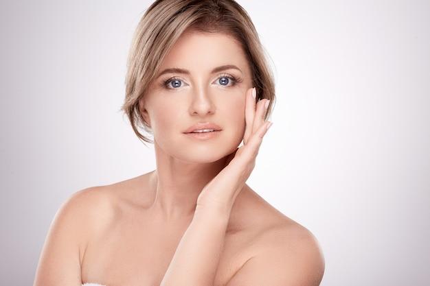 Aantrekkelijke vrouw van gemiddelde leeftijd met naakt make-up en naakte schouders poseren muur, schoonheid foto concept, huid en rimpels behandeling.
