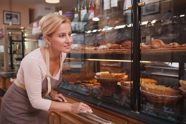 Aantrekkelijke vrouw van middelbare leeftijd die haar bedrijf van de bakkerijopslag runt, die opslagshowcase onderzoekt