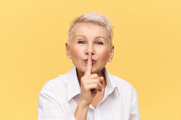 Aantrekkelijke vrouw van middelbare leeftijd in wit overhemd houdt wijsvinger bij haar mond, maakt een zwijg teken, zegt shh, vertel het aan niemand, vraagt je haar geheim te houden, met mysterieuze gezichtsuitdrukking