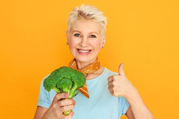 Aantrekkelijke vrouw van middelbare leeftijd met kort pixiehaar dat verse broccoli houdt en bij camera glimlacht die gezond biologisch voedsel kiest.