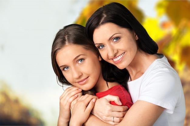 Aantrekkelijke vrouw van middelbare leeftijd omhelsd met haar tienerdochter, wazig gele bomen op de achtergrond