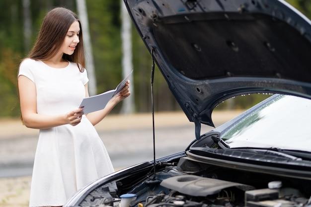 Aantrekkelijke vrouw voor haar auto kapotte auto met gebruikershandleiding