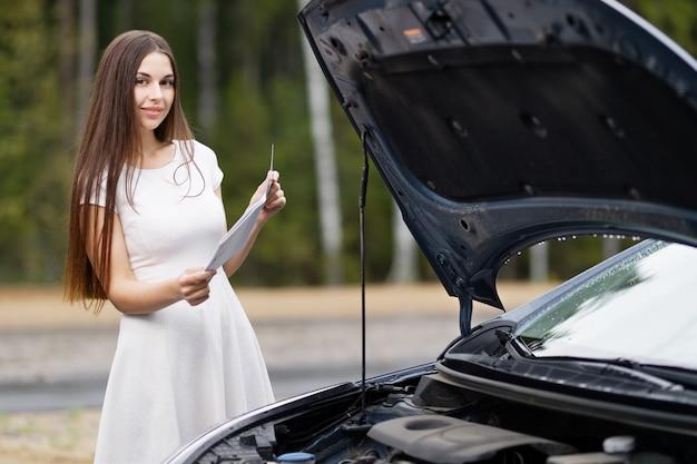 Aantrekkelijke vrouw voor haar auto kapotte auto