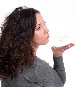 Aantrekkelijke vrouw waait harten op een witte achtergrond