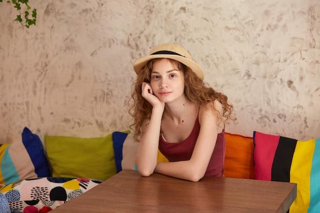 Aantrekkelijke vrouw zit aan tafel in restaurant op sofa met multi gekleurde kussens. jonge dame ziet er dromerig en ontspannen uit, gekleed in een casual outfit