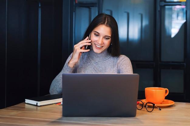 Aantrekkelijke vrouw zit aan tafel voor laptop en praat op mobiele telefoon, maakt aantekeningen in notitieblok.