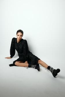 Aantrekkelijke vrouw zittend op de vloer modieuze kleding levensstijl lichte achtergrond