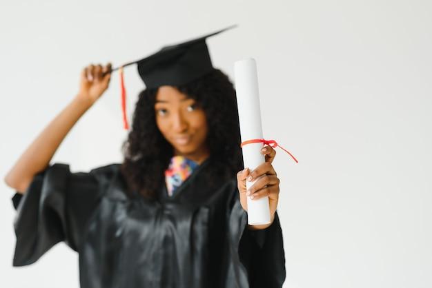 Aantrekkelijke vrouwelijke afro-amerikaanse universitair afgestudeerde op witte achtergrond