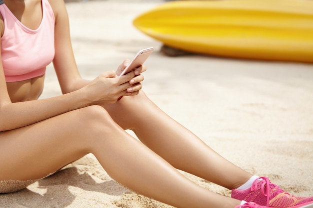 Aantrekkelijke vrouwelijke agent met gebruinde huid die roze sportbeha en loopschoenen dragen, zittend op strand met mobiele telefoon in haar handen, die rust na ochtendtraining in openlucht hebben. bijgesneden weergave