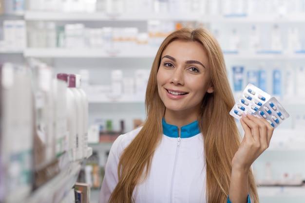 Aantrekkelijke vrouwelijke apotheker die jong vitaminepak aanbiedt, exemplaarruimte