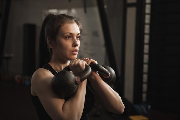 Aantrekkelijke vrouwelijke atleet trainen met kettlebells in de sportschool