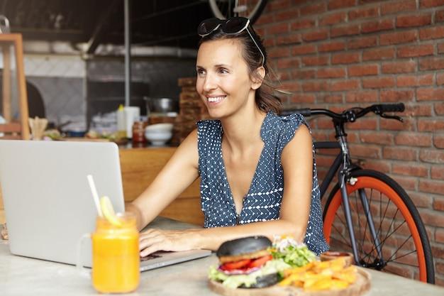 Aantrekkelijke vrouwelijke blogger die gelukkig glimlacht terwijl zij commentaren van volgers op haar blog leest