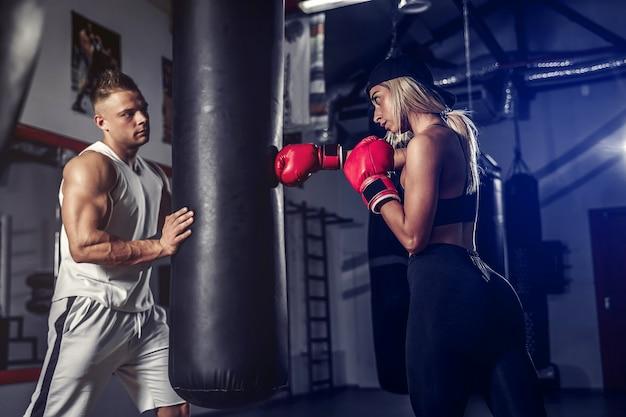Aantrekkelijke vrouwelijke bokser die traint door bokszak te raken