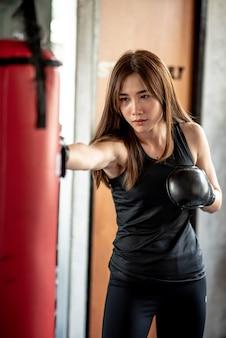 Aantrekkelijke vrouwelijke bokser training met kickboksen op sportschool met blackgloves.