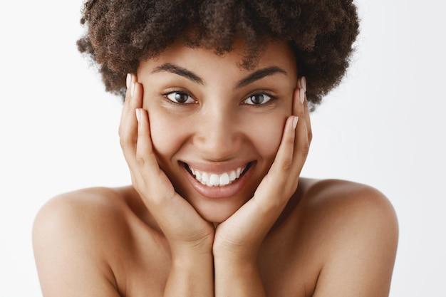 Aantrekkelijke vrouwelijke en natuurlijke afro-amerikaanse jonge vrouw met krullend haar en zuivere schone huid, gezicht aanraken en breed glimlachend van opwinding en geluk, naakt poseren over grijze muur