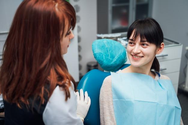 Aantrekkelijke vrouwelijke geduldige bezoekende tandarts.