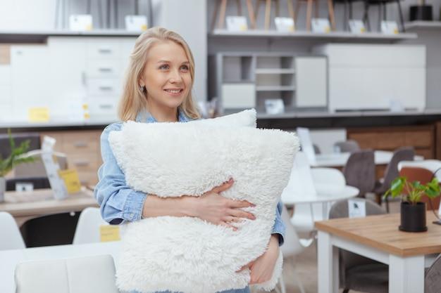 Aantrekkelijke vrouwelijke klant die bij meubilairopslag loopt, die pluizige hoofdkussens houdt