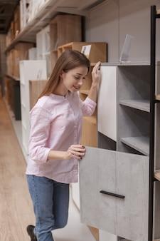 Aantrekkelijke vrouwelijke klant kasten te koop bij meubelwinkel onderzoeken