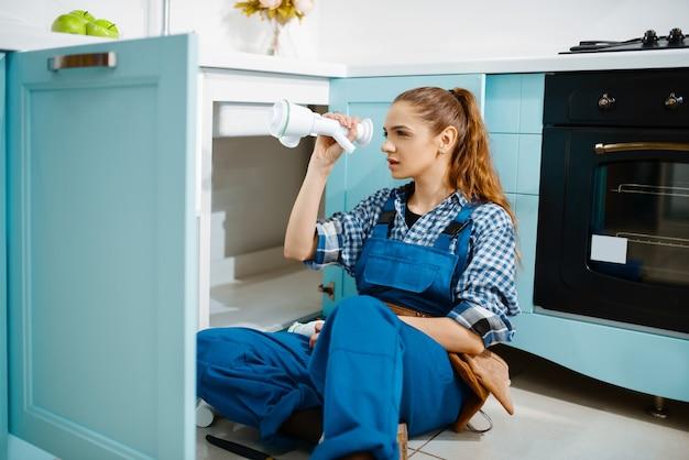Aantrekkelijke vrouwelijke loodgieter in uniform bevestigingsprobleem met afvoerpijp in de keuken. klusjesvrouw met gereedschapstas reparatie gootsteen, sanitair service aan huis