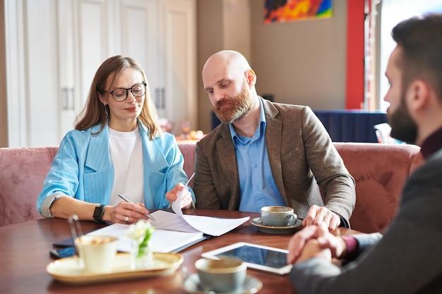 Aantrekkelijke vrouwelijke ondernemer zittend aan tafel in restaurant en ondertekening van documenten na een ontmoeting met nieuwe zakenpartners